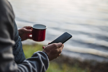 Man standing at lake, drinking coffee, using smartphone - KKA02784