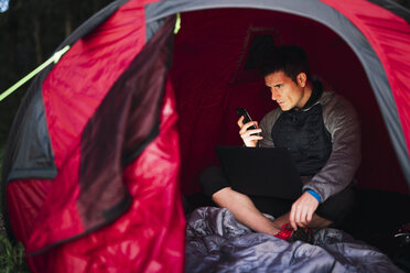 Man camping in Estonia, sitting in his tent, using smartphone - KKA02793