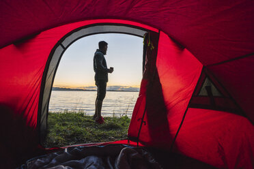 Man camping in Estonia, standing in front of tent, watching sunset - KKA02796
