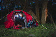 Man camping in Estonia, sitting in his tent, holding latern - KKA02799