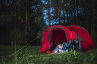 Man camping in Estonia, drawing in his sketchbook at night - KKA02802