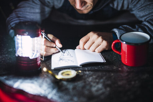 Man camping in Estonia, drawing in his sketchbook at night - KKA02805