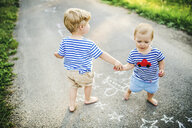 Toddler boy playing with his little sister outdoors - HAPF02790