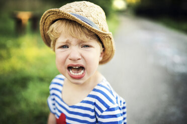 Portrait of screaming toddler wearing straw hat - HAPF02796