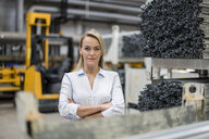 Blond woman in high rack warehouse - DIGF05418