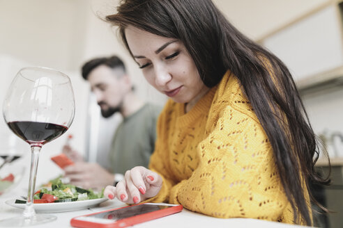 Young woman checking smartphone at lunch at home - KMKF00599