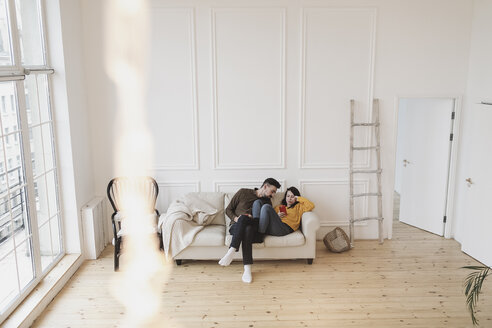 Couple sitting on the couch in the living room of new home looking at cell phone - KMKF00602
