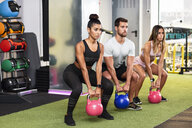 Young people doing kettle ball workout in a gym - JSMF00482