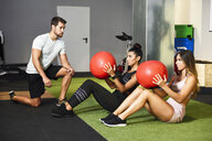 Young people doing ab training with fitness balls - JSMF00485
