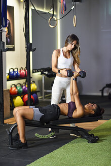 Personal trainer assisting client with weight training, lifting dumbells, lying on bench - JSMF00494