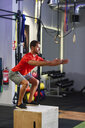 Man doing box jumps in a gym - JSMF00503