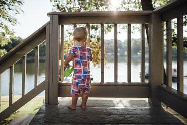 Rear view of baby boy standing by wooden railing against lake - CAVF50591