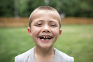 Close-up portrait of happy boy standing at park - CAVF50594