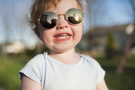 Close-up portrait of cute happy baby boy wearing sunglasses while standing in yard - CAVF50633