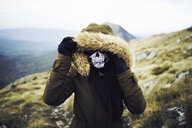 Female hiker wearing mask while standing on mountain against sky during winter - CAVF50645