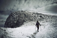 Rear view of female hiker walking on snow covered mountain against cloudy sky - CAVF50648