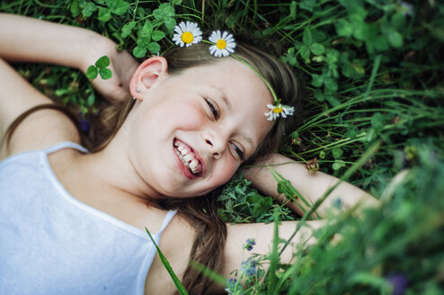 High angle view of happy girl looking away while lying on field amidst plants at park - CAVF50654