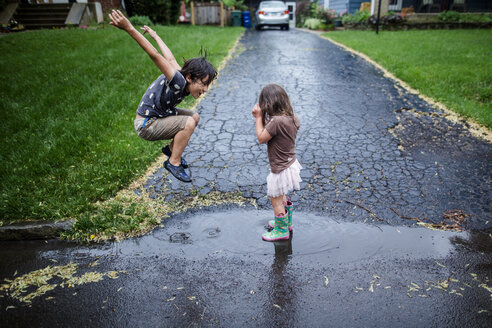 Side view of playful siblings enjoying on wet road during rainy season - CAVF50657