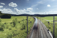 Blurred motion of train moving on railroad tracks amidst green landscape against blue sky - CAVF50660