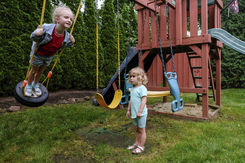 Sad girl looking at happy sister swinging on tire swing at playground - CAVF50666