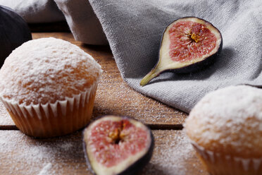 High angle view of muffins with figs and napkin on wooden table - CAVF50672