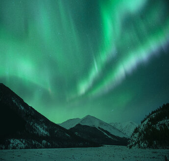 Low angle majestic view of aurora borealis over mountains during winter - CAVF50705