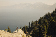 High angle view of hiker on cliff by lake during foggy weather - CAVF50717
