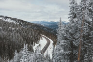 Aerial view of mountain road against cloudy sky during winter - CAVF50726