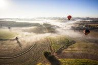 Aerial view of hot air balloons flying over landscape against sky during sunny day - CAVF50729