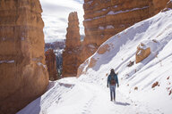 Rear view of female hiker walking on snowcapped mountain amdist rock formations at Bryce Canyon National Park - CAVF50744