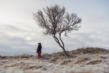 Girl standing by bare tree against sky on field - CAVF50747