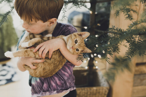 High angle view of boy carrying cute kitten while standing by plant at home - CAVF50750