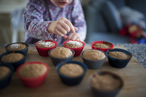 Midsection of girl garnishing cupcakes on wooden table at home - CAVF50759