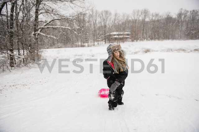 Girl wearing warm clothing while walking with sled on snowy field against trees during snowfall - CAVF50762