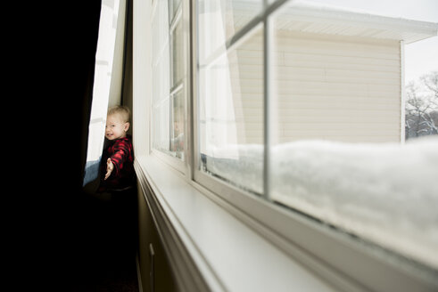 Portrait of playful boy standing behind curtains at home - CAVF50765