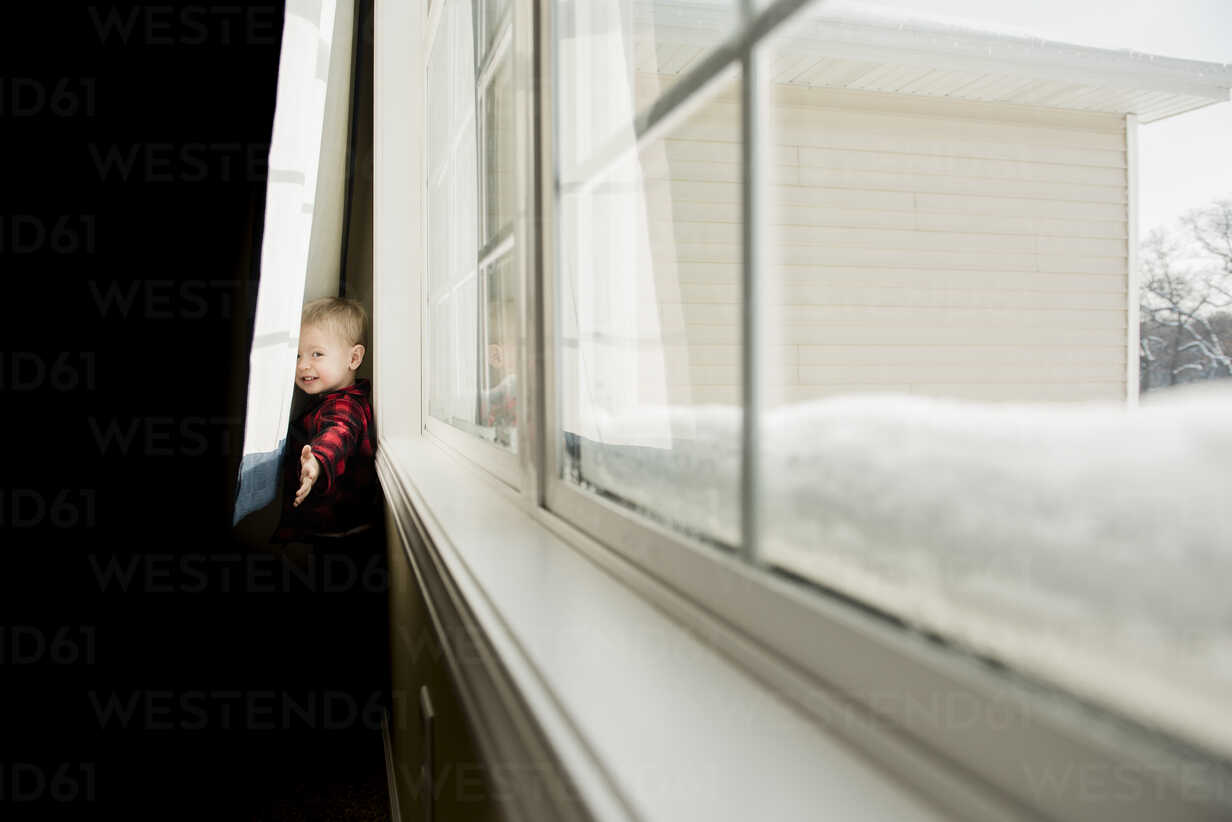 Portrait of playful boy standing behind curtains at home - CAVF50765 - Cavan Images/Westend61