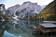 Cottage in calm lake by mountains against sky during winter - CAVF50789
