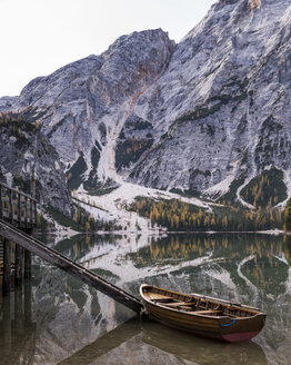 Boat moored on calm lake by mountain during winter - CAVF50795