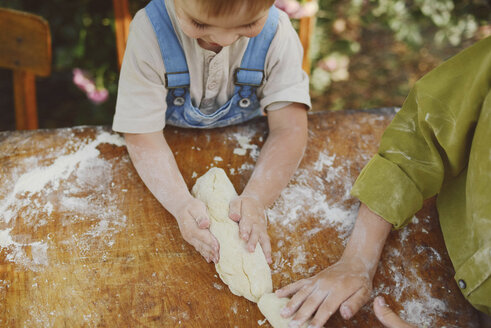 High angle view of brothers kneading dough on table in yard - CAVF50819