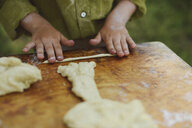 Midsection of boy preparing dough on wooden table at yard - CAVF50825