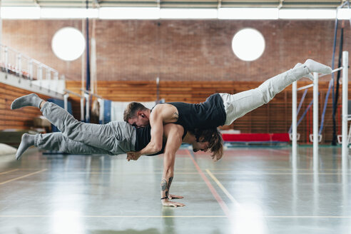 Full length side view of gymnasts practicing handstand at gym - CAVF50852