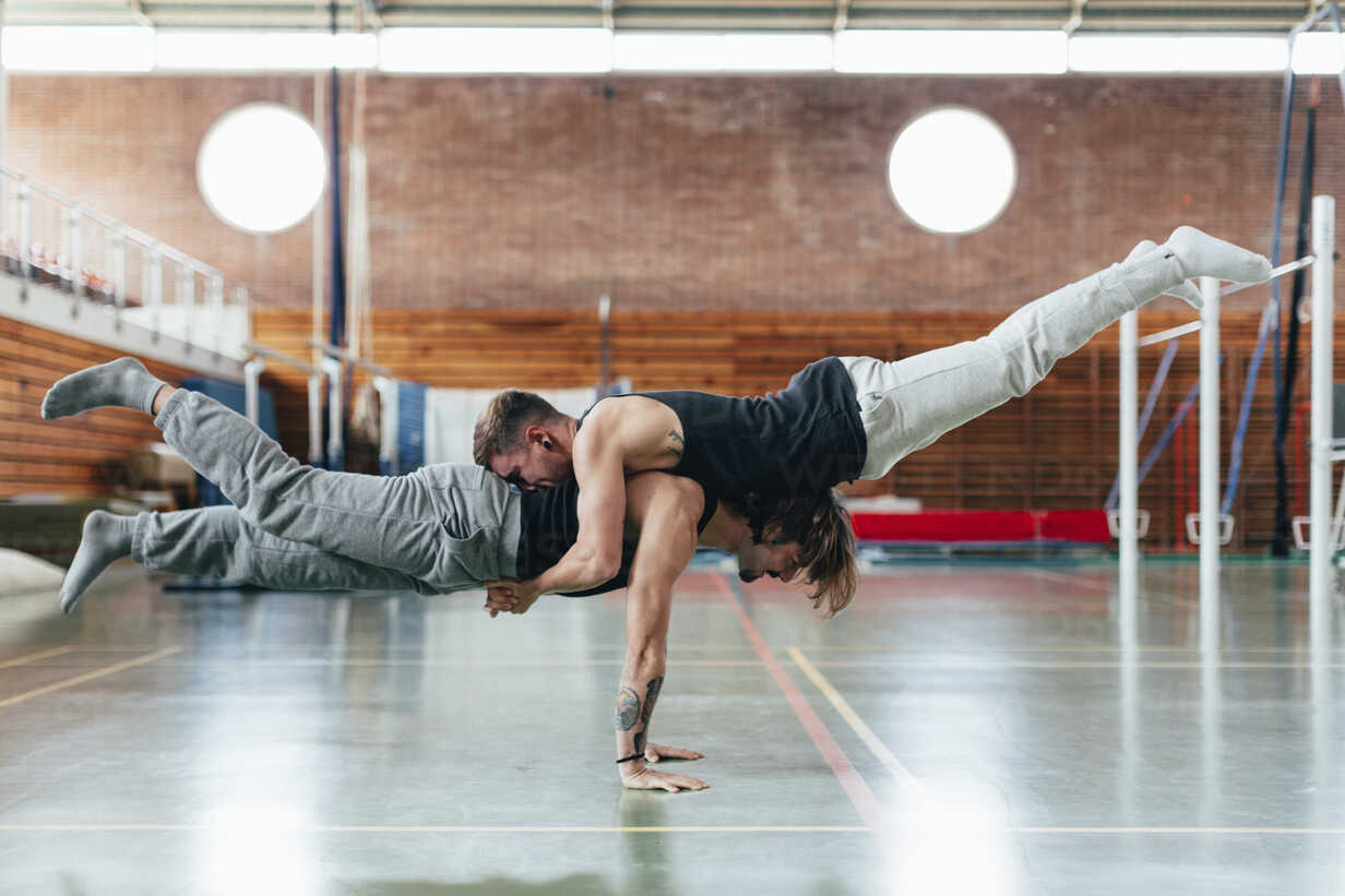 Full length side view of gymnasts practicing handstand at gym - CAVF50852 - Cavan Images/Westend61