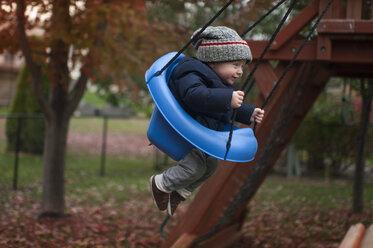 Full length of baby boy swinging on swing at park - CAVF50876