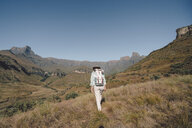 Rear view of woman with backpack hiking on grassy field against clear blue sky - CAVF50882