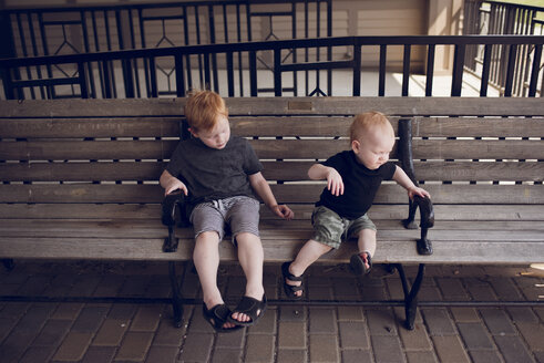 Brothers sitting on wooden bench at park - CAVF50894
