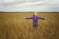 Carefree girl with arms outstretched standing amidst soybean's field against cloudy sky - CAVF50900