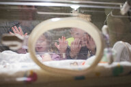 Low angle view of siblings looking at newborn brother at hospital - CAVF50903