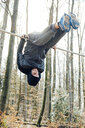 Low angle view of man hanging upside down on pole in forest against sky - CAVF50921
