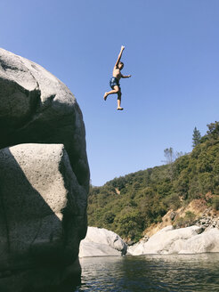 Low angle view of carefree shirtless boy jumping in Yuba River from cliff - CAVF50924