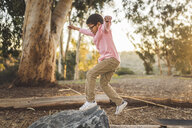 Side view of boy jumping on rock in forest - CAVF50987